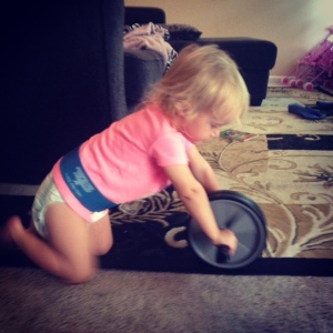 My daughter Hartley pushing an ab wheel while wearing a mini band as a belt